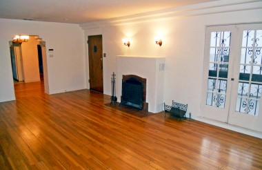 Gorgeous original hardwood floors in living room with period fireplace and original French doors leading to the beautiful courtyard!