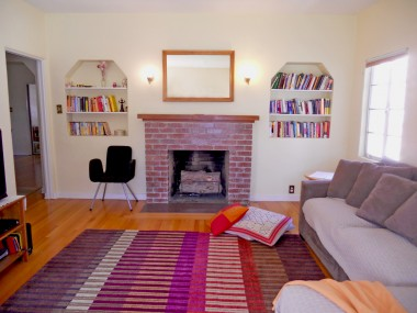 Huge living room with gorgeous original hardwood floors, high ceiling, and wood-burning and gas log fireplace.