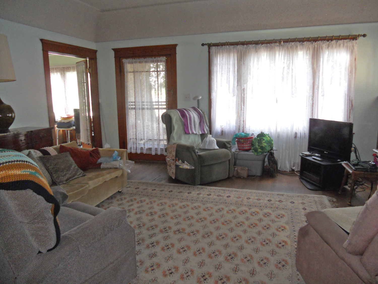 Spacious living room with lots of original woodwork throughout including hardwood floors.