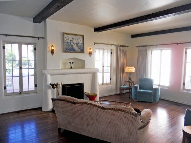 Gracious step-down living room with majestic fireplace, beamed ceiling and original hardwood floors.