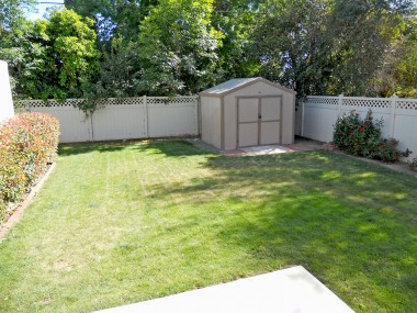 Pool-size backyard, with beautiful roses, vinyl fencing, and a spacious private area behind garage perfect for gardening.