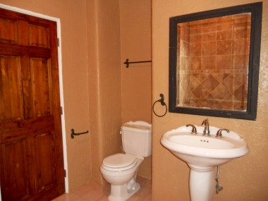 Remodeled bathroom with tile floor, pedestal sink and newer toilet.