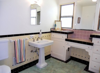 Spacious bathroom with original pedestal sink, toilet and dressing table.