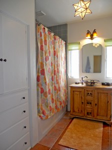 Full bathroom in hallway with tile floor, new Kohler soaking tub and newer tiled shower enclosure. Spacious linen cabinetry and modern bowl sink.