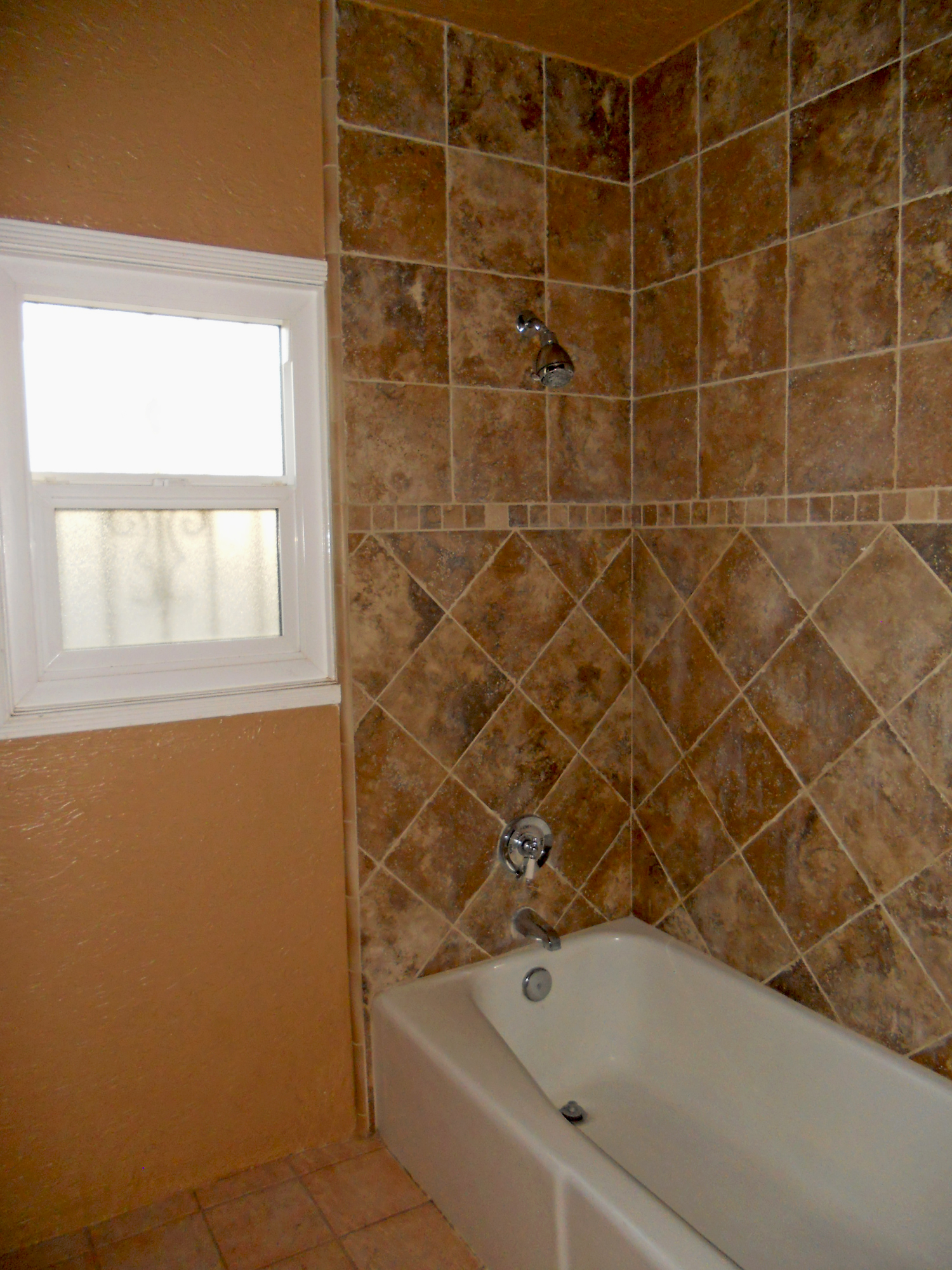 Gorgeous re-tiled tub/shower enclosure in the remodeled bathroom.