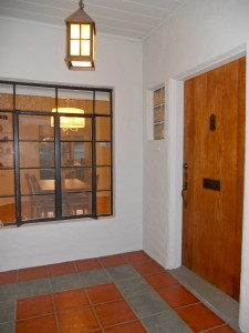 Spacious tiled entry with original front door.