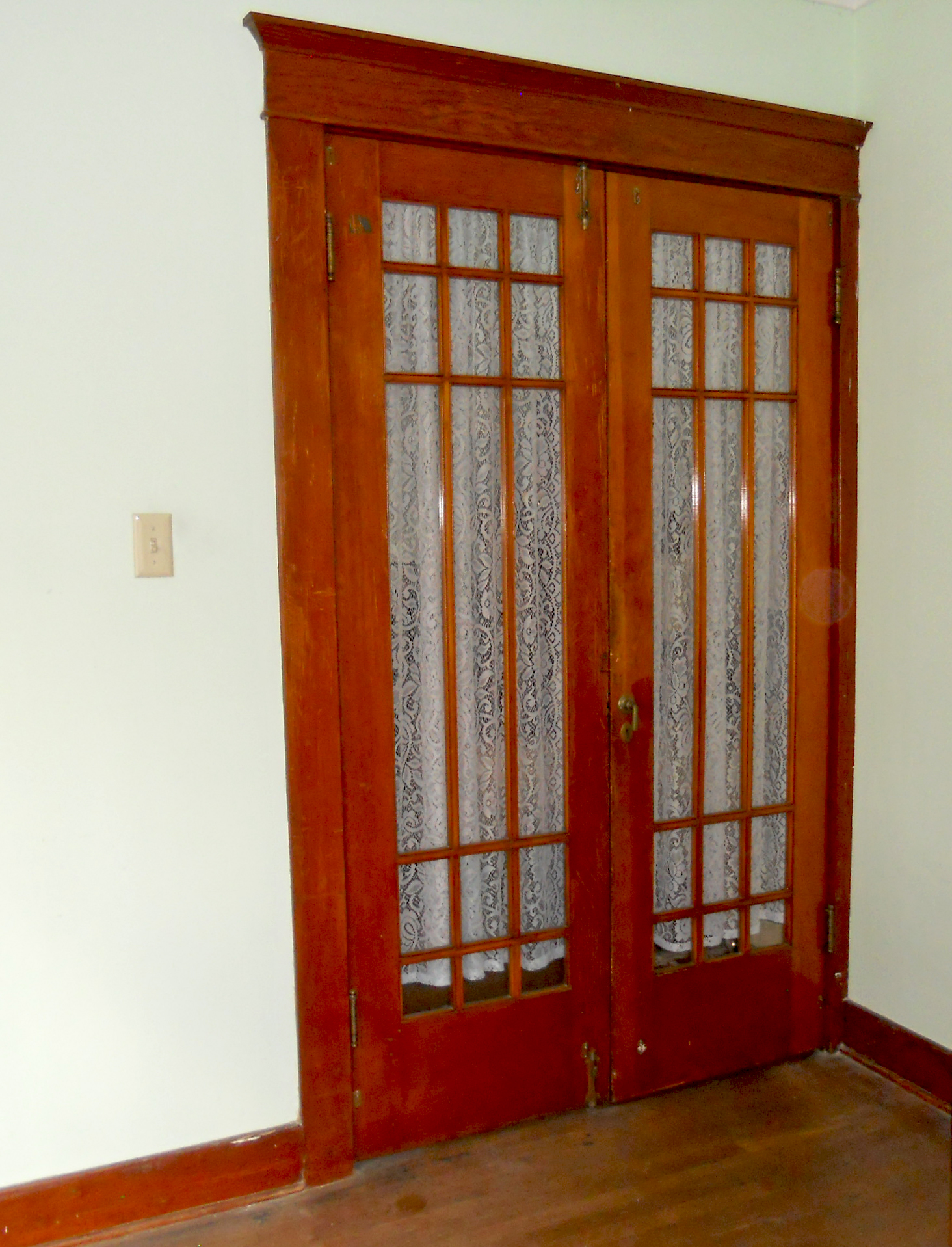 Gorgeous original interior French doors separating living room and front bedroom.