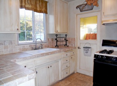 Lovely remodeled kitchen with lots of cabinetry, tumbled marble counter tops, marble flooring, gas stove, garbage disposal, pull-out drawers, and a designated cabinet for microwave.