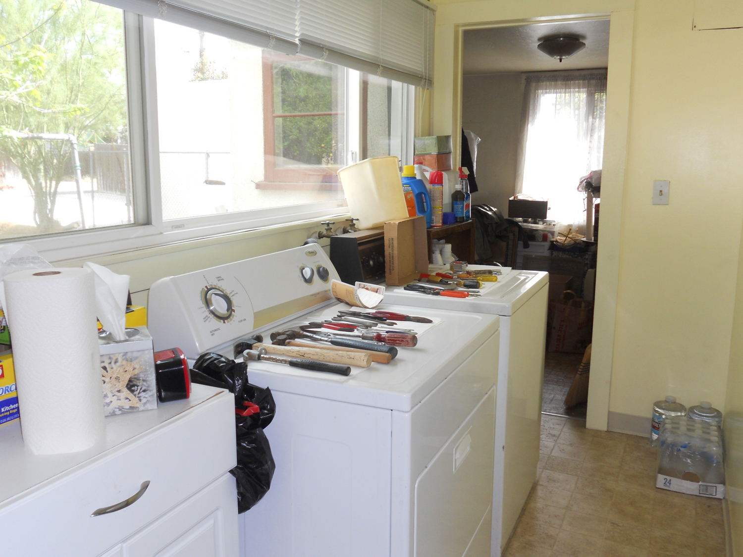 Separate indoor laundry room, with bonus room in the back. Homeowners are in the process of preparing for an estate sale; hence, the clutter.