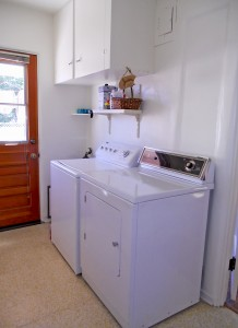 Spacious laundry room with attached closet that once had a toilet, but now that it's removed, the plumbing is still intact for future renovation.