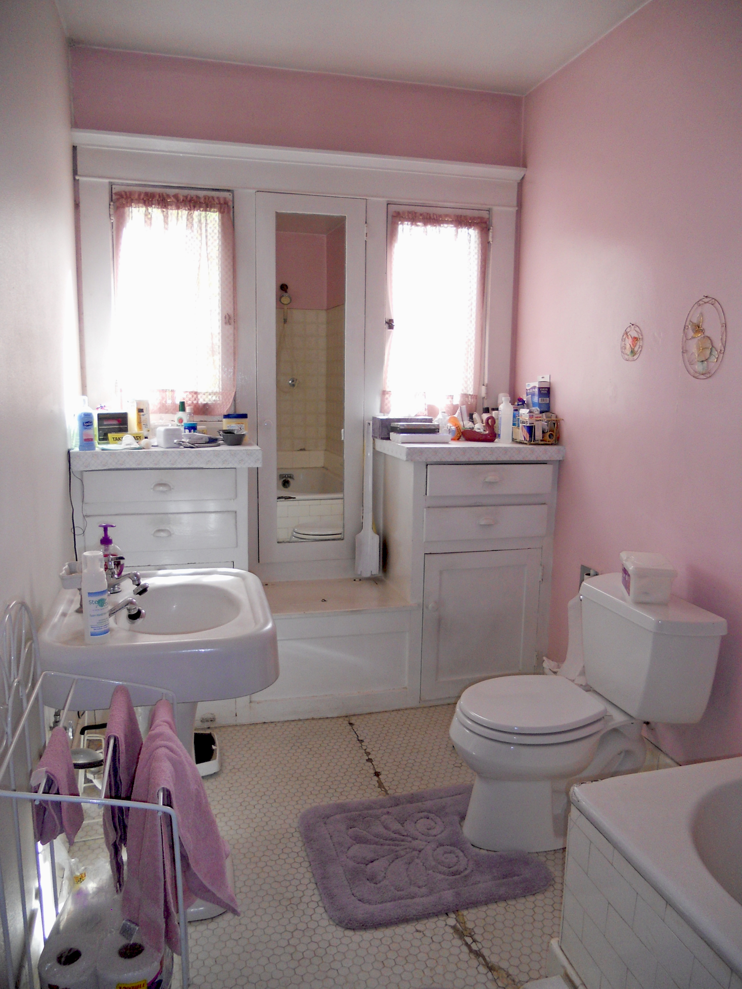 The main bathroom with built-ins, pedestal sink and original tub. The original tile floor has some cracking, but there are wonderful Riverside artisans who can replace this flooring to match the original tiles.