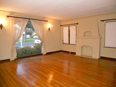 Spacious living room with decorative fireplace, large picture window and original hardwood floors.