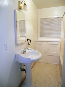 Full bathroom with newer pedestal sink and tiled shower surround, but original tiled floor and built-in cabinetry (very retro).