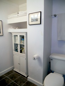 Alternate view of hallway bathroom with linen storage.
