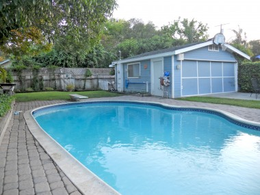 Another view of pool with 2-car garage and grassy area in which the kids can romp.