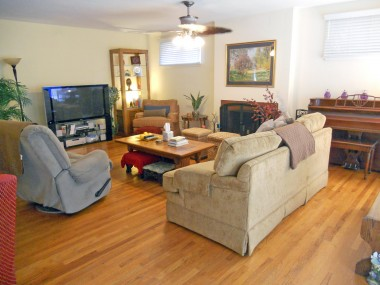 Spacious living room with hardwood floors, fireplace and floor-to-ceiling windows overlooking serene backyard.