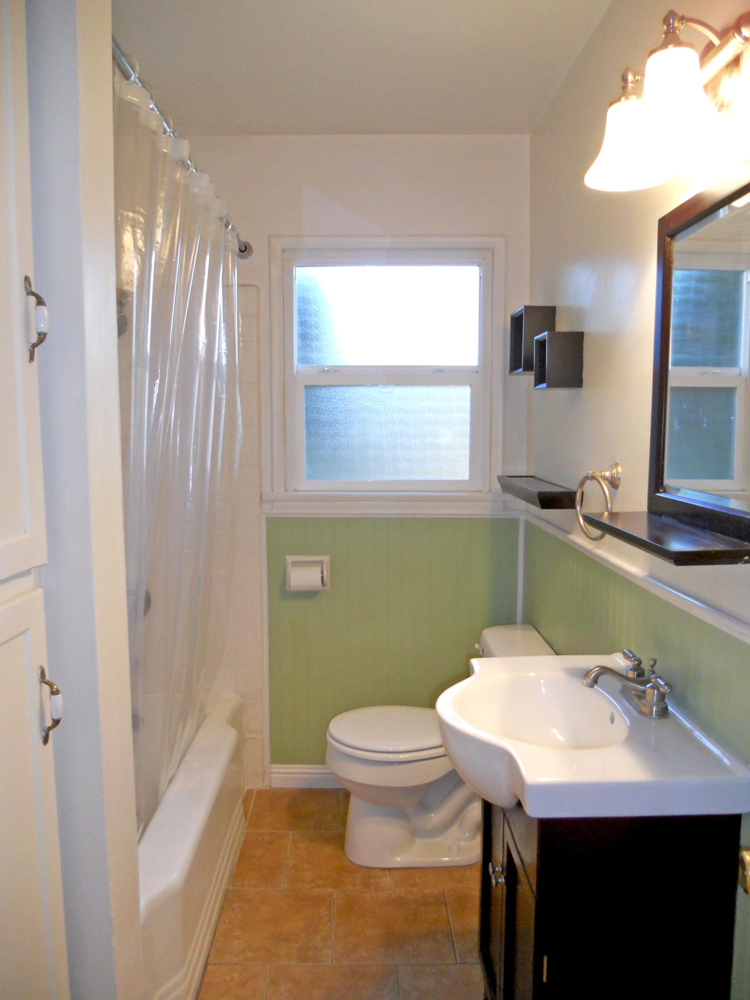 Updated bathroom with tile floor, newer vanity, wainscoting and deep linen closet.