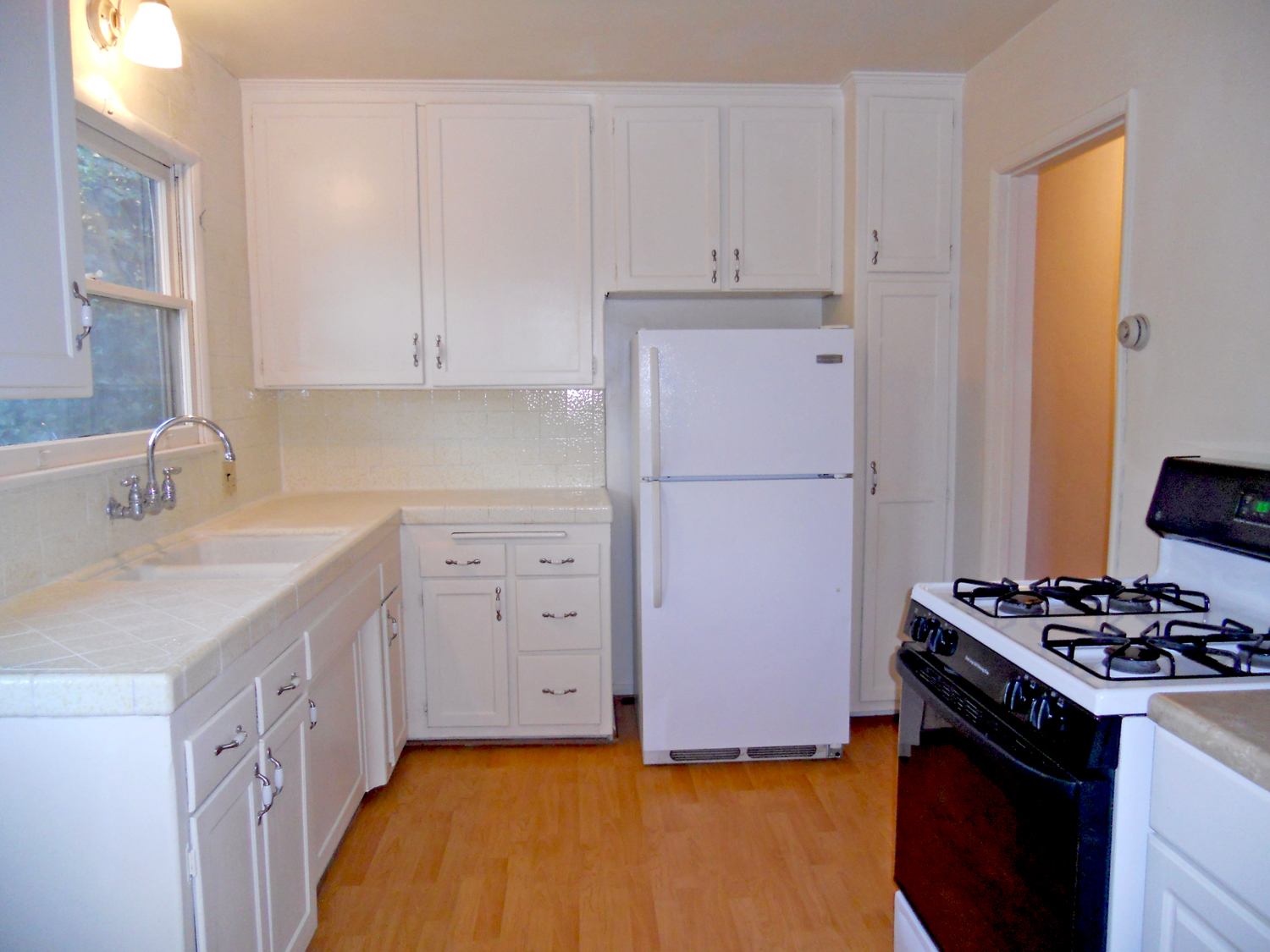 Lovely kitchen with tiled counter tops, new gas stove, and refrigerator stays too!