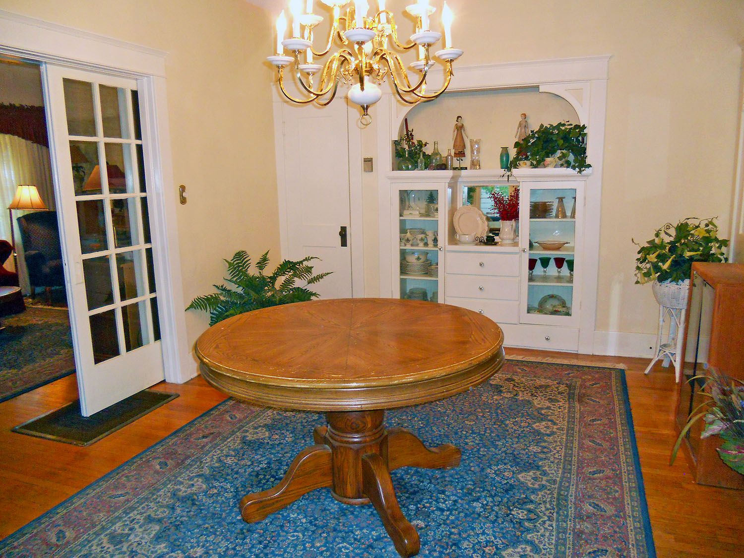 Formal dining room with original hardwood floors (old floor furnace that is no longer needed as this home now has central air/heat) and a built-in China hutch.
