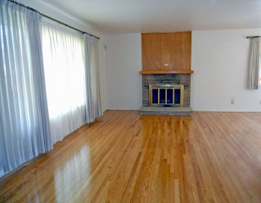 Spacious living room with fireplace and gleaming refinished hardwood floors.