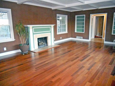Large living room with fireplace, newer wood floors, beamed ceiling and a large bay window overlooking Riverside.