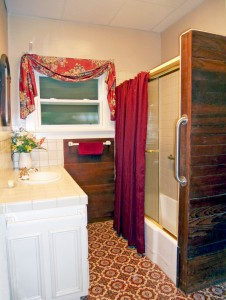 Updated bathroom with tile counter, tiled shower in immaculate condition, and newer frosted double pane window.