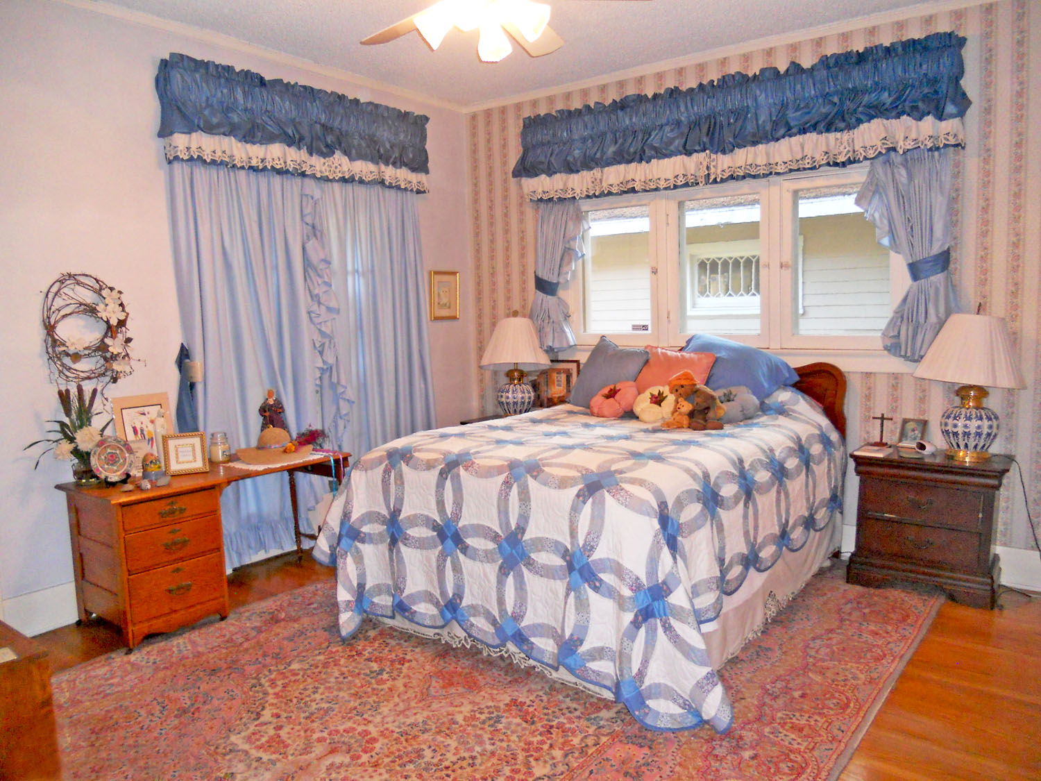 Large front bedroom with 9-ft ceiling, original hardwood floors, ceiling fan, and walk-in closet.