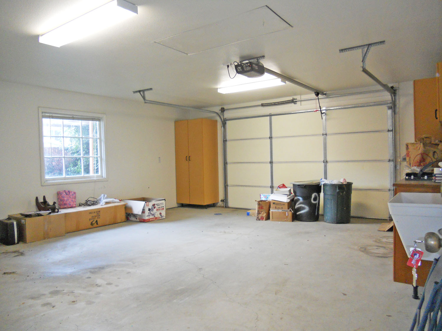 Finished garage with pull-down ladder to attic storage. There is also a convenient utility sink and cabinetry.