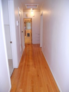 Recently refinished hardwood floors in hallway leading to beds and baths.