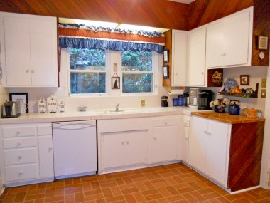 Kitchen with tiled counter tops, dishwasher and gas stove.