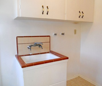 Convenient indoor laundry room with utility sink and cabinetry.