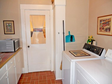 Convenient indoor laundry room with lots of cabinetry and peek-a-boo door that leads to the kitchen.
