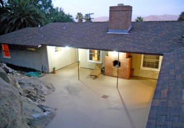View of back of home at dusk - note the huge intriguing boulders that make up part of the patio.