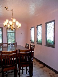 Formal dining room with coved ceiling and original diamond pane windows. Wood flooring needs to be refinished or possibly replaced.