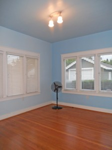 Back bedroom with hardwood floors, high ceiling, and original light fixture.