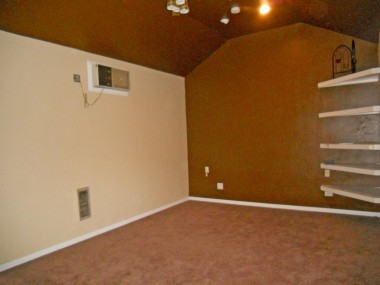 Permitted bonus room attached to back of garage with heat/air and high ceiling and built-in shelving.