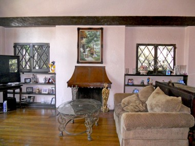 Living room fireplace flanked by built-in shelving. Gotta love those charming original diamond pane windows too.