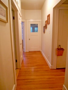Hallway with hardwood floors that were refinished just a few years ago.  Door with basket leads to attic.
