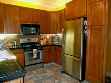 Alternate view of kitchen. Note the accent lighting for counter tops and above cabinetry.