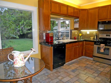 Remodeled eat-in kitchen with tile floor, tile counters, stainless steel appliances that stay, including dishwasher.