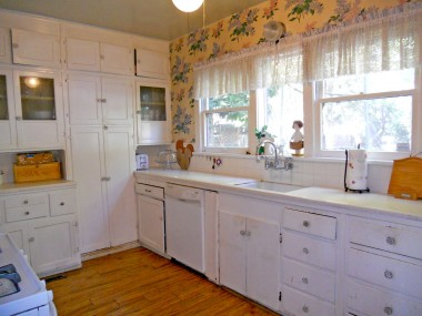 Kitchen with lots of cabinetry, gas stove and dishwasher. Laundry room is adjacent to kitchen.