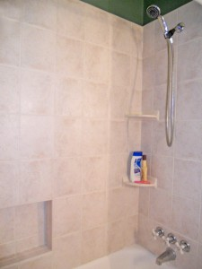 Remodeled tiled tub/shower with built-in soap/shampoo alcove.