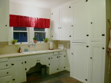 Bright kitchen with lots of original charming cabinetry. Homeowners may leave behind the portable dishwasher.