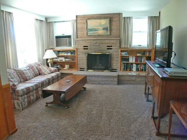Spacious family room with large picture window, fireplace and built-in shelving.