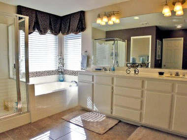Private master bathroom with soaking tub, shower, and tile floor.