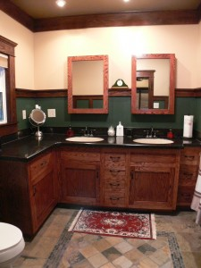 Private master bathroom with dual sinks, tile floor and recessed lighting.