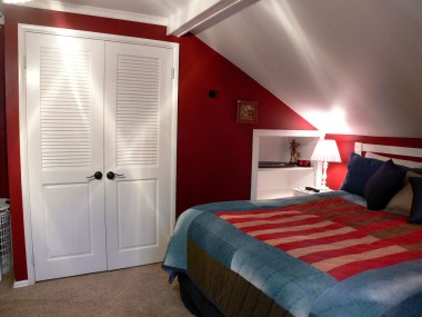 Alternate view of upstairs bedroom with built-in bookshelves and ample closet space.