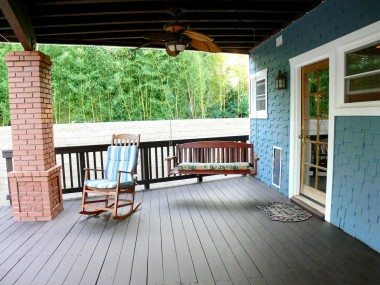 Alternate view of redwood deck and beamed ceiling with ceiling fan. Note the convenient doggie door too!