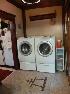 Laundry room with tiled Riverside rain cross emblem and French door to deck overlooking the resort-like backyard.