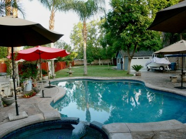 Lovely 15-yr-old Bogner pool/spa overlooking the vast expanse of resort-like backyard perfect for family gatherings and volleyball/badminton/football games! A couple of the cement tables with umbrellas will stay with the home.